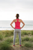 Fitness female athlete standing towards the sea Stock Image