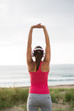 Fitness female athlete stretching arms towards the sea Stock Images