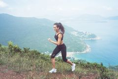 Fitness female athlete wearing black sportswear doing cardio exercise, running in mountains with inspirational sea view.  Royalty Free Stock Image