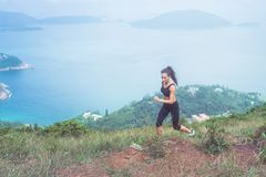 Fitness female athlete wearing black sportswear doing cardio exercise, running in mountains with inspirational sea view.  Stock Photos