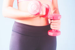 Fitness female in black pants and pink sport bra holding red dumbbells Stock Photo