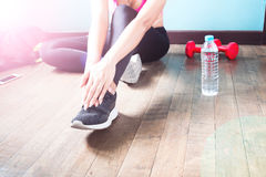 Fitness female in black pants and sneaker stretching after workout Royalty Free Stock Photography