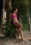 Fitness Female Brunette Model Wearing Bikini And Sunglasses Leaning Against Tree Holding Her Hair Back On Beach Royalty Free Stock Photo