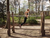 Fitness female doing parallel bar dips Stock Photography
