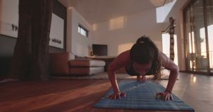 Fitness female doing push ups at home stock footage