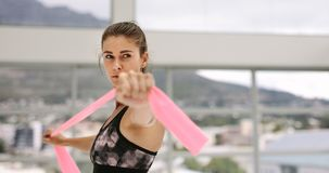 Fitness female doing stretching workout. Fit woman using a resistance band in her exercise routine at gym. Fitness female doing stretching workout Royalty Free Stock Images