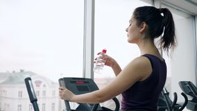 Fitness female drinks mineral water from plastic bottle during workout in gym stock video footage