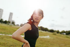 Fitness female on field glancing back. Shot of confident young woman looking back while standing outdoors. Fitness female on field in morning glancing back Stock Image