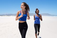Fitness female friends jogging on the beach Stock Photos