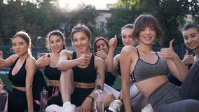 Fitness female good-looking group sitting on the outdoor stadium`s floor and showing sign ok on camera after fitness