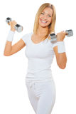 A fitness female holding two dumbbells and smiling Stock Photography