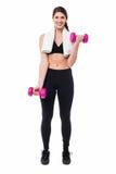 Fitness female instructor lifting dumbbells Royalty Free Stock Image