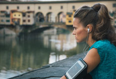 Fitness female with mp3 player staying close to Arno river Stock Image