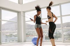 Female partners jumping together with skipping rope. Fitness female partners jumping together with skipping rope in gym. Women friends workout together in gym Royalty Free Stock Images