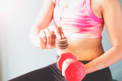 Fitness female in pink sport bra holding red dumbbell and snack in other hand Royalty Free Stock Image
