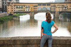 Fitness female in sportswear looking on Ponte Vecchio Royalty Free Stock Photos