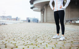 Fitness female standing on sidewalk in city. Cropped shot of a young woman standing on urban street while out for a run in the city. Fitness female standing with royalty free stock photo