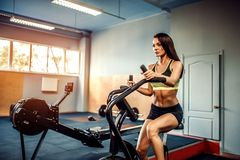 Fitness female using air bike for cardio workout at crossfit gym. Stock Photos