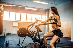 Fitness female using air bike for cardio workout at crossfit gym. Stock Image