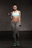Fitness female woman with muscular body, do her workout with dumbbells Royalty Free Stock Photo
