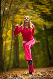 Fitness fit woman blond girl doing exercise in autumnal park. Sport. Stock Images