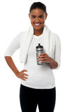 Fitness freak holding sipper, towel around her neck Royalty Free Stock Image