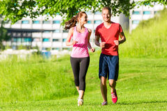 Fitness Friends running together. Through park Royalty Free Stock Photography