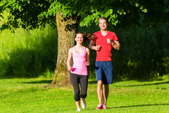 Fitness Friends running together in park Stock Photo
