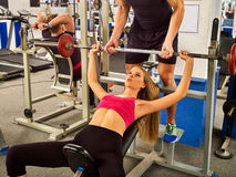 Fitness friends workout gym. Woman working on bench press. Royalty Free Stock Photos
