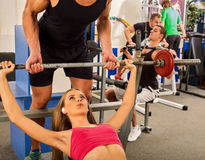 Fitness friends workout gym. Woman working on bench press. She lifting barbell. Trainer backs girl while taking exercises. Girl breathes deeply and heavily Royalty Free Stock Images