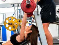 Fitness friends workout gym. Woman working on bench press. She lifting barbell. Trainer backs girl while taking exercises. Group work people on treadmill Royalty Free Stock Photography