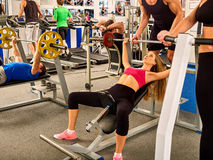 Fitness friends workout gym. Woman working on bench press. She lifting barbell. Trainer backs girl while taking exercises. Group work people on treadmill Royalty Free Stock Photos