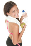 Fitness girl. Fitness woman. Smiling happy asian fitness girl with water bottle and fruit. Gorgeous smiling mixed race chinese / caucasian model isolated on Stock Image