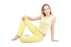 Fitness girl. Slim smiling girl in yellow sportive clothes sitting on white background Royalty Free Stock Photography