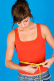 Fitness girl. Young fitness girl with measure tape Royalty Free Stock Photo
