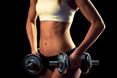 Fitness girl - attractive young woman working out with dumbbells Royalty Free Stock Photos