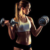 Fitness girl - attractive young woman working out with dumbbells. Attractive young woman working out with dumbbells Royalty Free Stock Images