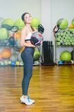 Fitness girl with ball. Fitness girl poses with a ball after a workout. The concept of health, sports Royalty Free Stock Photos