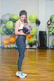 Fitness girl with ball. Fitness girl poses with a ball after a workout. The concept of health, sports Stock Image