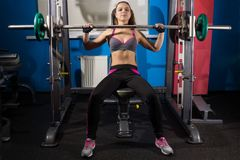 Fitness girl and a barbell. Stock Images