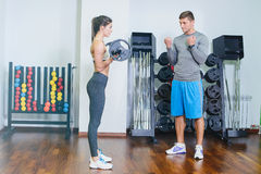 Fitness girl with a barbell, coach. Fitness girl training with a barbell, the coach. The concept of sport, health Royalty Free Stock Photos