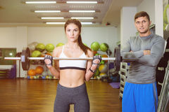 Fitness girl with a barbell, coach. Fitness girl training with a barbell, the coach. The concept of sport, health Royalty Free Stock Image
