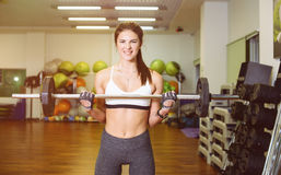 Fitness girl with a barbell, coach. Fitness girl training with a barbell, the coach. The concept of sport, health Royalty Free Stock Images