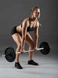Fitness girl with barbell doing deadlift Royalty Free Stock Image