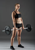 Fitness girl with barbell doing deadlift Royalty Free Stock Photos