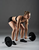 Fitness girl with barbell doing deadlift Royalty Free Stock Images