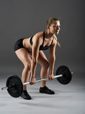 Fitness girl with barbell doing deadlift Stock Photos