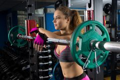 Fitness girl and a barbell. Fitness girl and a bar in the gym. Exercises. Dark background Royalty Free Stock Photography