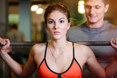 Fitness girl with a barbell working with a trainer. The concept of health, sports Stock Image