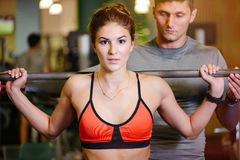 Fitness girl with a barbell working with a trainer. The concept of health, sports Royalty Free Stock Images